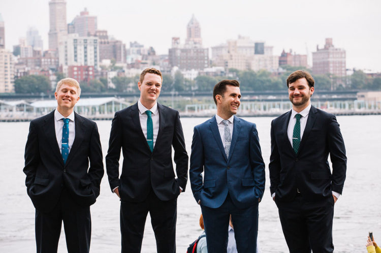 The groomsmen were wearing black suits and jewel blue and green ties