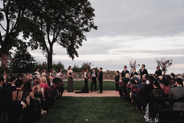 The wedding ceremony took place in the garden of the castle, the black chairs were decorated with deep red blooms
