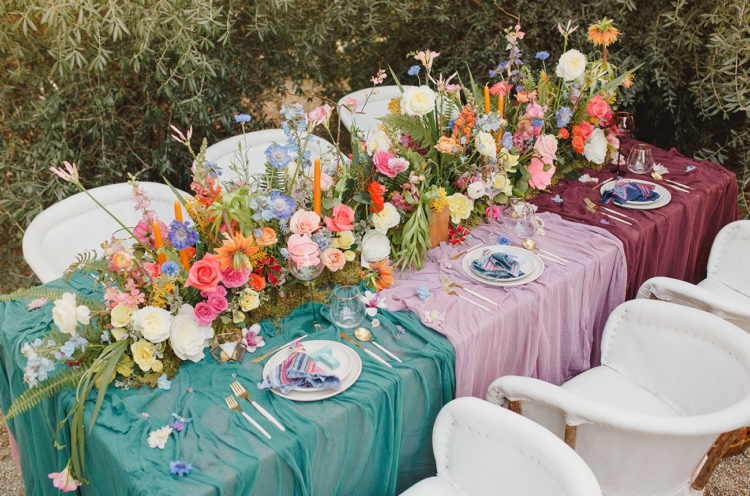 The wedding table was dressed up with colorful textiles, bold flowers and striped napkins and orange candles
