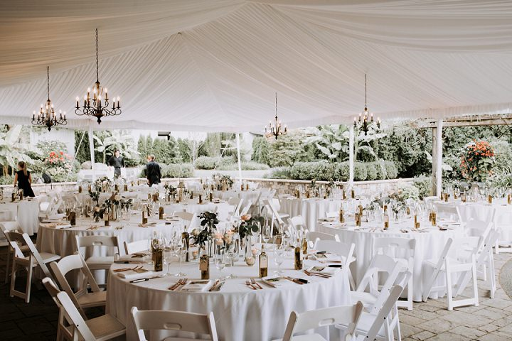 The wedding tent was decorated with glam chandeliers and in a neutral color palette