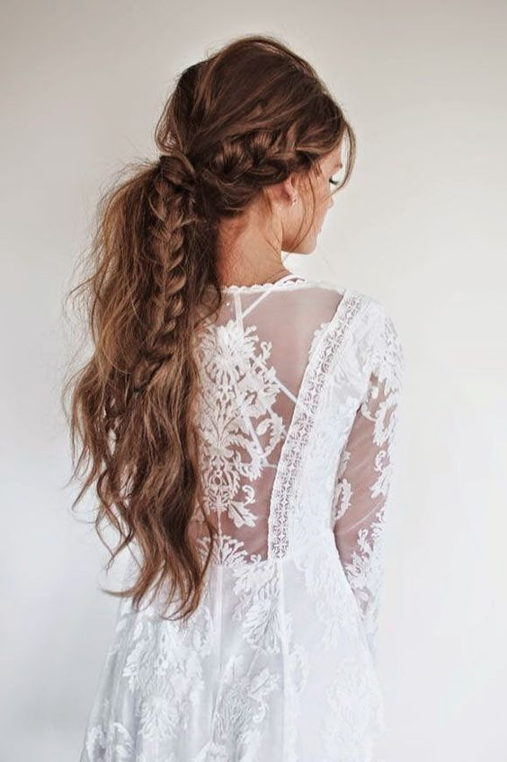 a boho messy ponytail with a large braid incorporated in it