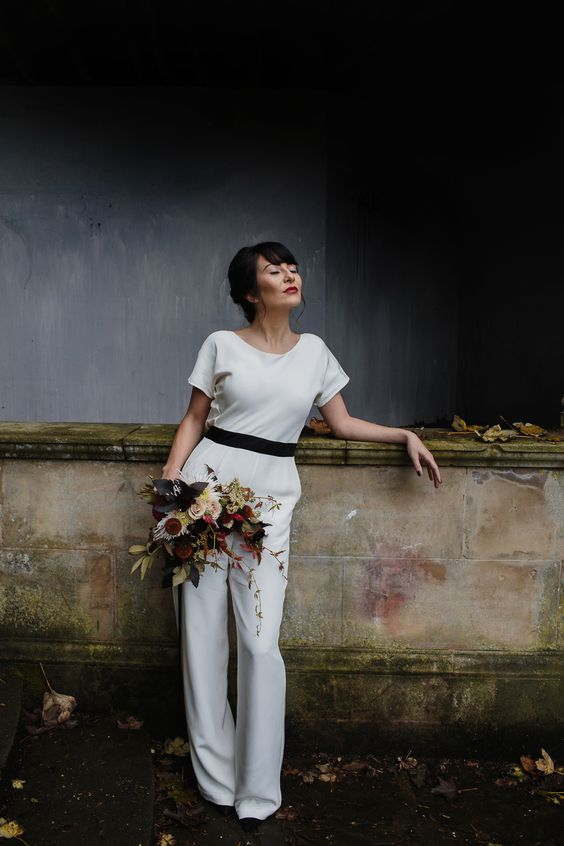 a creamy bridal jumpsuit with short sleeves and a black sash to accent the waist