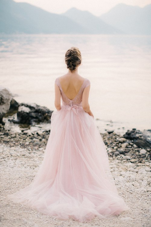 a delicate light pink wedding dress with a lace bodice, an open back on buttons and a light tulle full skirt