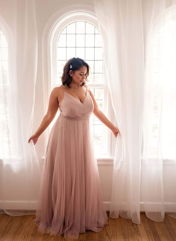 a gorgeous blush spaghetti strap bridesmaid's dress with a deep V-neckline looks very cute