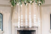 07 a large greenery hanging with a piece of driftwood and escort cards hanging down on strings