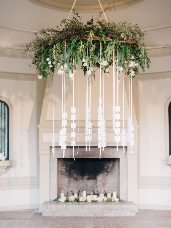 a large greenery hanging with a piece of driftwood and escort cards hanging down on strings