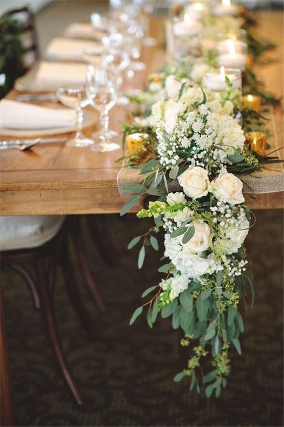 a lush greenery and flower table runner in green and white can fit many color schemes and styles