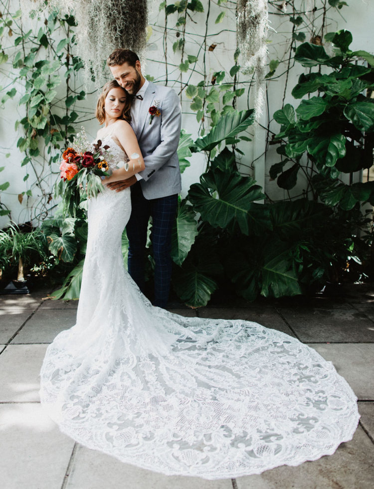 a mermaid lace wedding gown with a V-neckline, low back, spaghetti straps and a large train