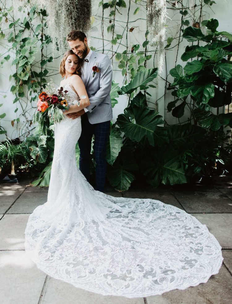 a mermaid lace wedding gown with a V neckline, low back, spaghetti straps and a large train