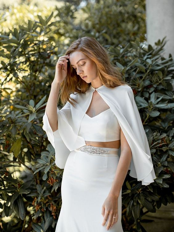 a minimalist bridal separate with an embellished belt and a cape for a trendy look