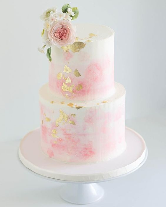 a pink watercolor wedding cake with gold leaf topped with pink blooms for a garden wedding