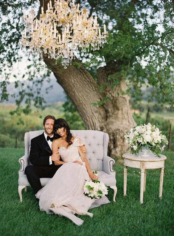 a romantic glam space with a vintage sofa and an overiszed glam chandelier for the wedding portraits