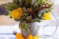 07 a textural floral centerpiece with much greenery, leaves, yellow roses and tulips and a yellow bow