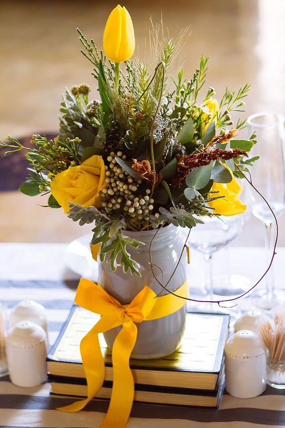 a textural floral centerpiece with much greenery, leaves, yellow roses and tulips and a yellow bow