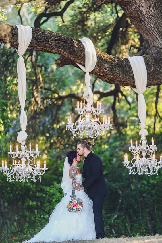 large glam chandeliers on ethereal fabric create an intimate and comfy space for a wedding