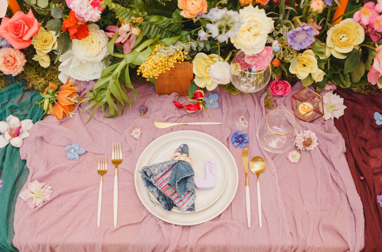 Handmade candle holders, wood burnt table numbers and gold flatware made the tablescape cooler