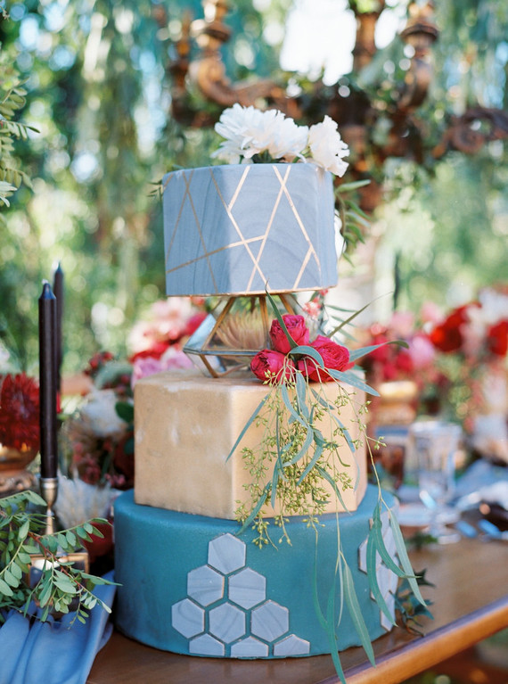 The wedding cake consisted of three parts, a marble blue one with gold geometry, a gold geometric one and a blue tier with hexagon decor