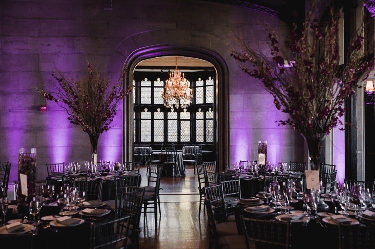 The wedding venue, which was the castle, featured gorgeous glam chandeliers, there were purple and red centerpieces and floating candles