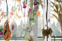 08 a boho wedding arch decorated with greenery and blooms hanging down from it