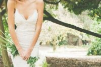 08 a lace sheath wedding dress with spaghetti straps is completed with a greenery crown