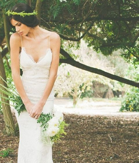 a lace sheath wedding dress with spaghetti straps is completed with a greenery crown