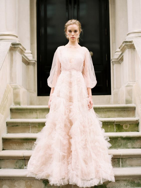 a light pink wedding dress with a V neckline, puff tulle sleeves and a skirt with pink tulle appliques for a chic look