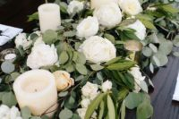 08 a lush greenery garland with white blooms and pillar candles is a gorgeous table decoration