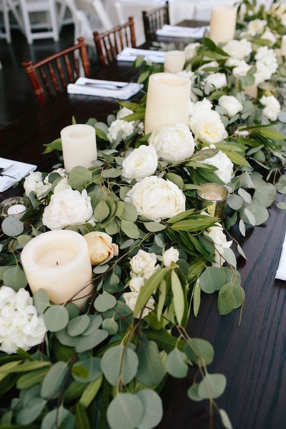 a lush greenery garland with white blooms and pillar candles is a gorgeous table decoration