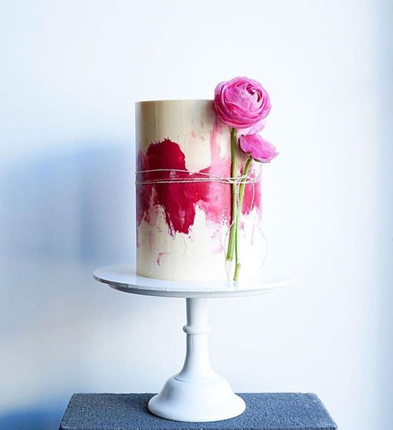 a modern watercolor wedding cake with hot pink decor and pink blooms attached