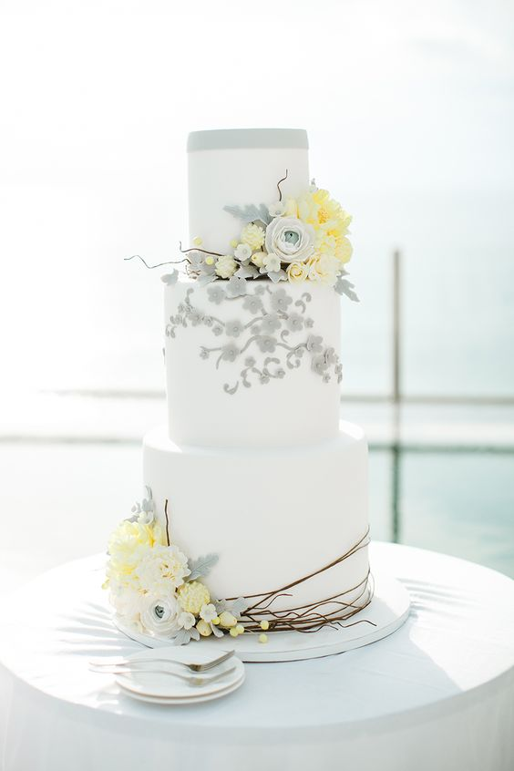 an ethereal wedding cake with sugar grey and yellow flowers looks very modern and chic
