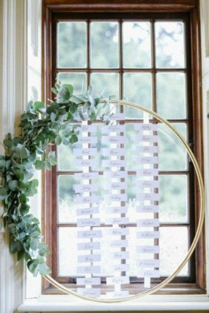 an oversized hoop with escort cards in the center and a lush greenery garland