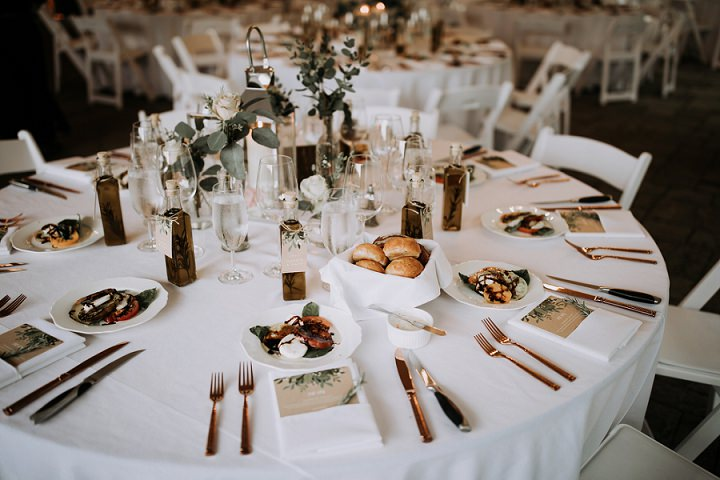 The wedding table setting was done with white and blush roses, eucalyptus, candle lanterns and herb infused oil was given as favors