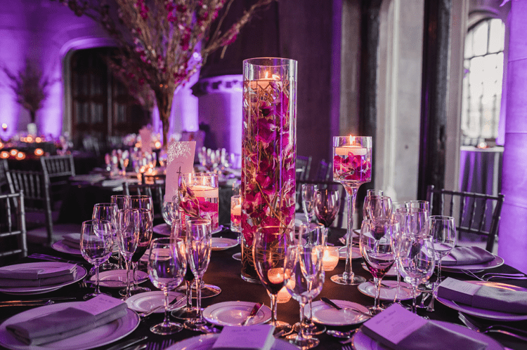 The wedding tablescape was done with purple blooms and floating candles, it looked very beautiful