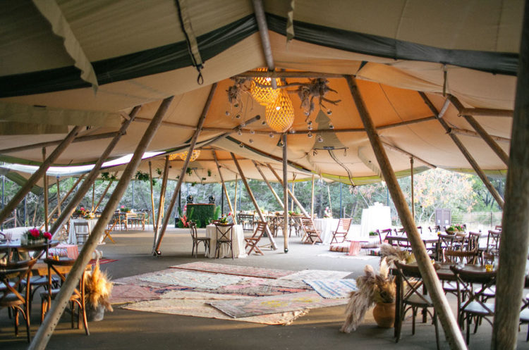 The wedding tents were done with boho rugs, pampas grass, antlers and fresh greenery for a boho feel