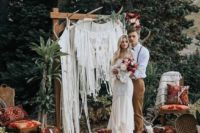 09 a bold ceremony space with a macrame wedding arch, rugs, pillows and antlers