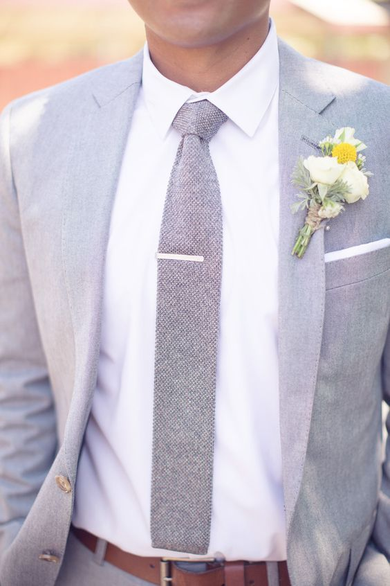 a groom wearing a grey suit, a grey tie and a yellow boutonniere looks very stylish and relaxed