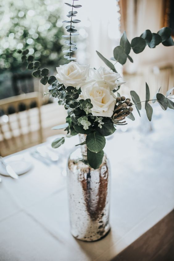 a mercury glass vase with white roses and fresh eucalyptus is an elegant centerpiece