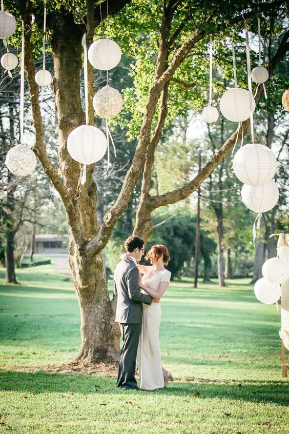 paper and macrame lanterns hanging on the tree create a backdrop for a wedding ceremony