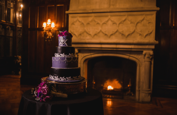 The wedding cake was a purple and black one, decorated with hite cream patterns and topped with purple blooms