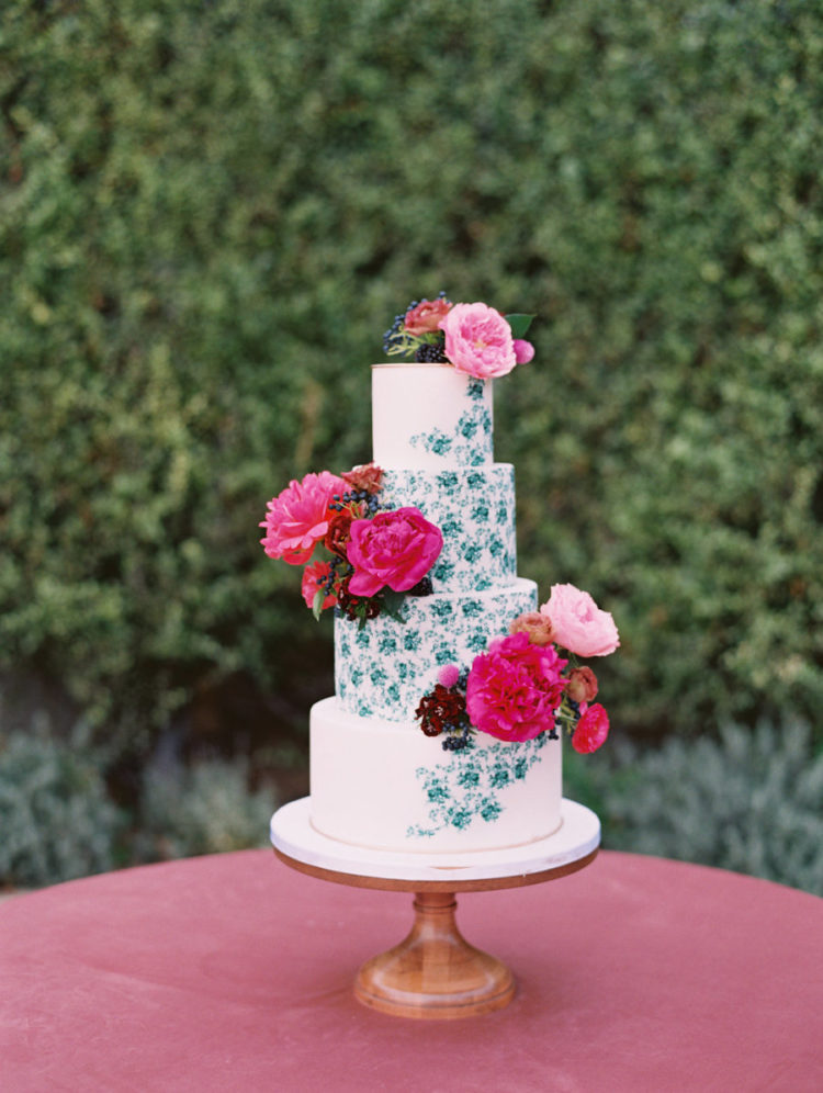 The wedding cake was half painted and decorated with the same fuchsia and pink florals
