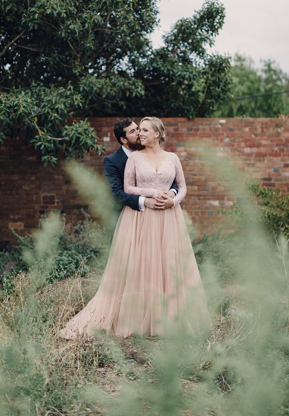 a dusty pink wedding dress with a pleated skirt and an embellished bodice with long sleeves