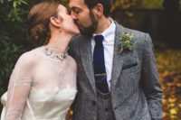 10 a grey tweed three-piece suit with a navy tie and handkerchief and a greenery boutonniere