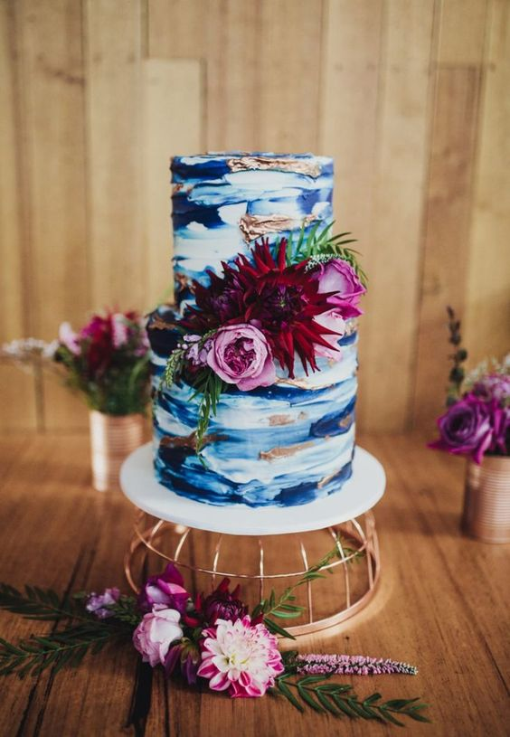 a very bold watercolor wedding cake in the shades of blue, with copper touches and pink and burgundy blooms