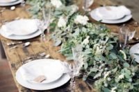 10 a very lush greenery table runner with berries and white blooms over a naked table