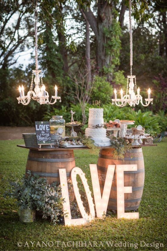 a wedding cake display on barrels and with marquee letters plus glam chandeliers
