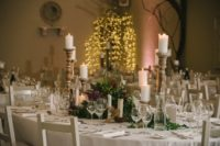 The tables were done with textural greenery and flower centerpieces and candles in vintage candle holders