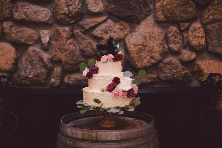 The wedding cake was baked by the mother of the groom, it was a buttercream one decorated with bold blooms, greenery and with toppers