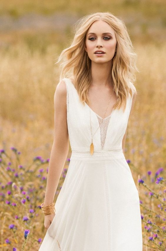 a boho thick strap A line wedding dress with a lace covered plunging neckline and a flowy skirt