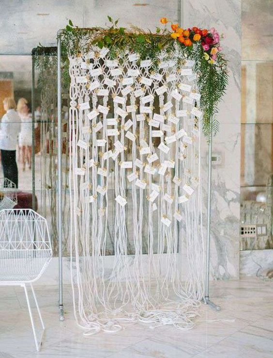a boho woven seating chart with a greenery garland and bold florals on the corner