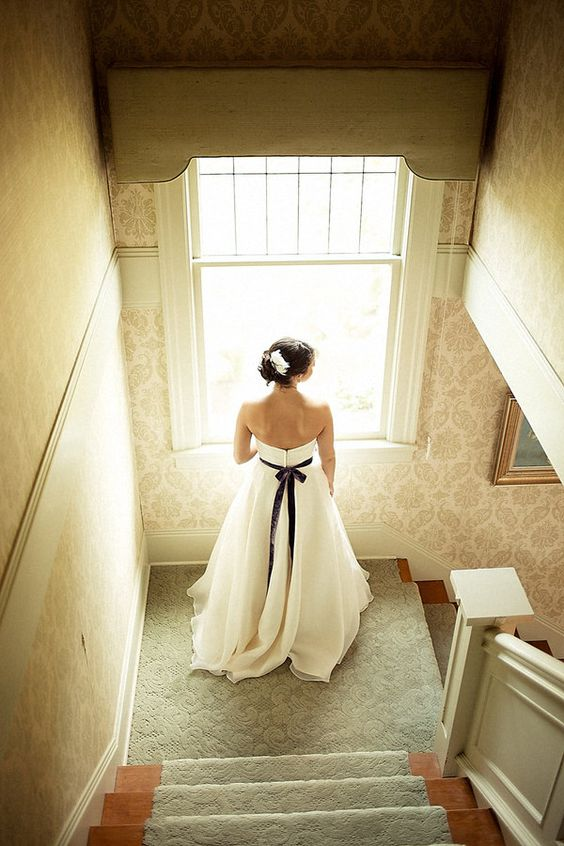 a bride wearing a deep purple velvet wedding sash for a colorful touch and to highlight the waist